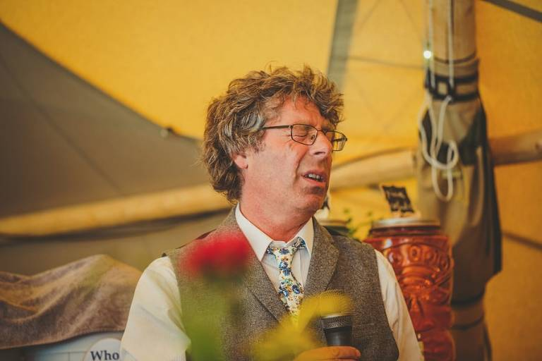 The grooms father closes his eyes during his speech in the tipi