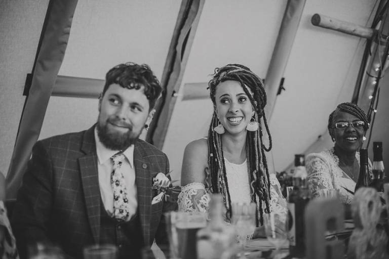 The bride and groom listen to the father of the grooms speech in the tipi