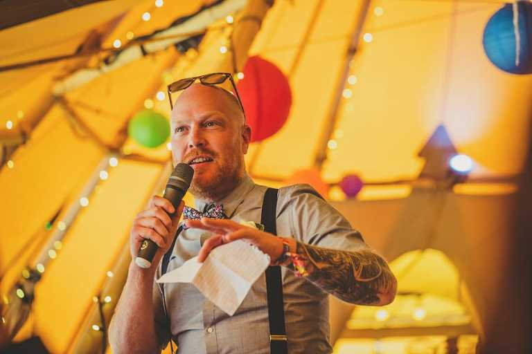 The best man stands up in the tipi at Hadsham Farm and delivers his speech