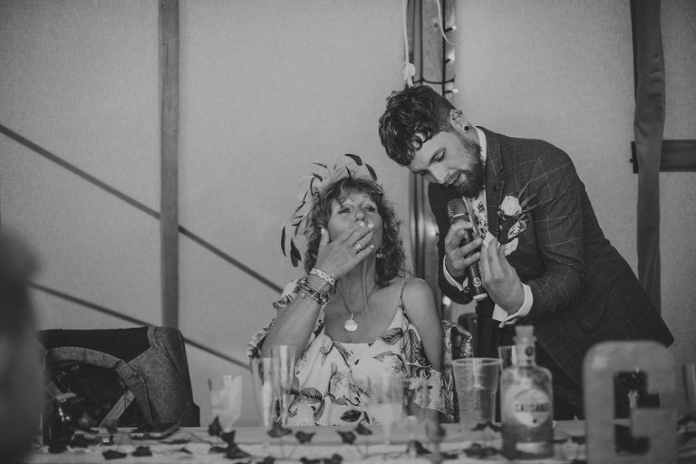 The groom shows his mother a ticket as she blows a family friend a kiss