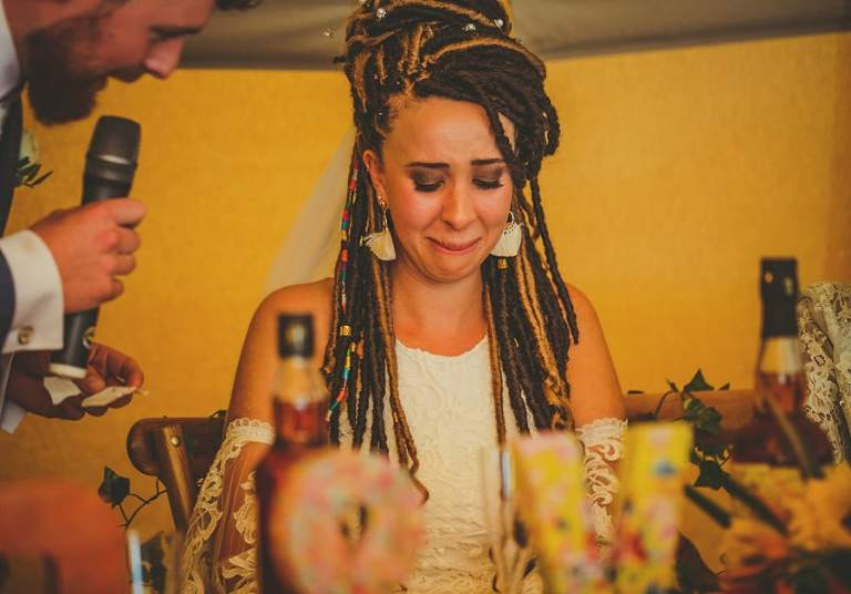 The bride cries as the groom stands over her with a microphone