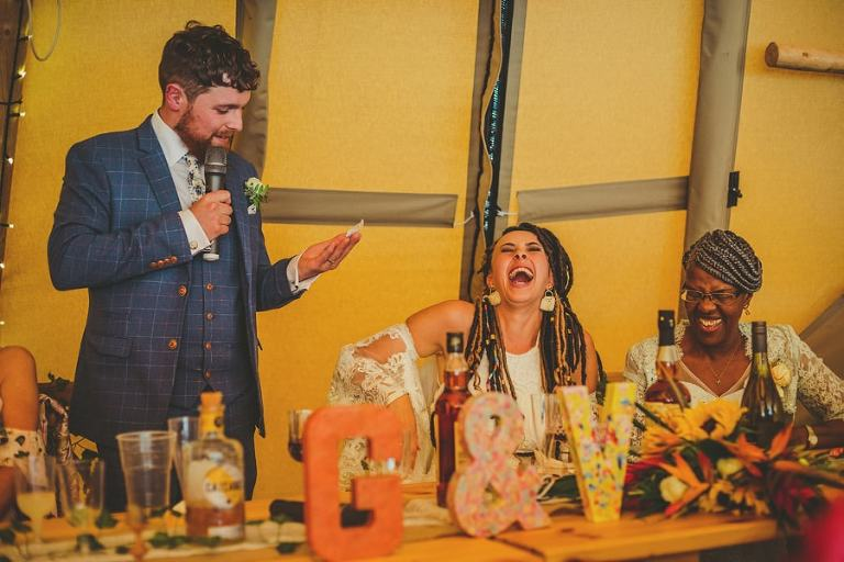 The bride and her mother laugh at a joke told by the groom