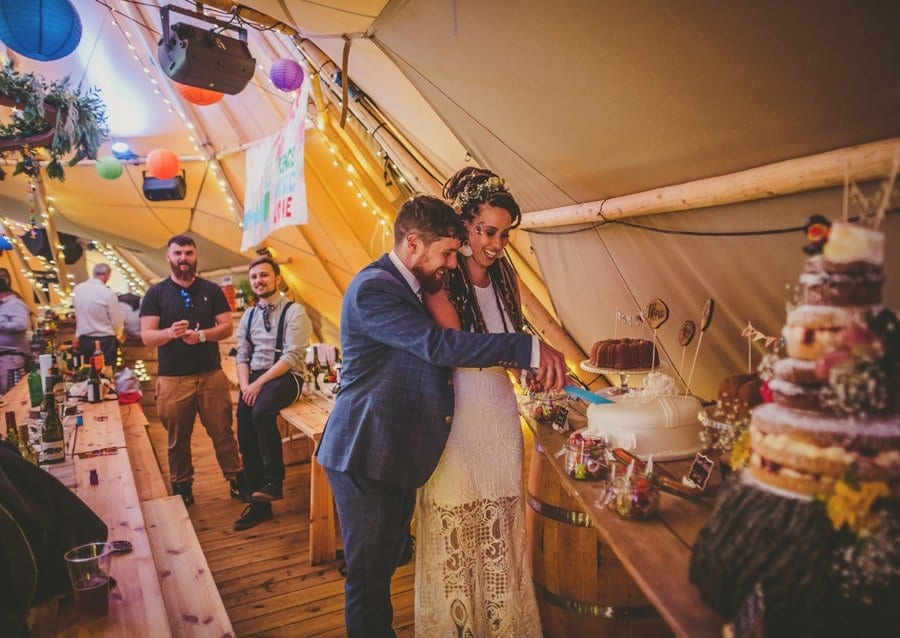 The bride and groom cut the cake in the tipi at Hadsham Farm.