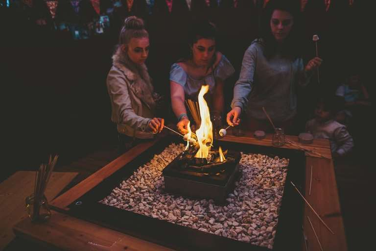 Wedding guests toasting marshmallows in the tipi at Hadsham Farm