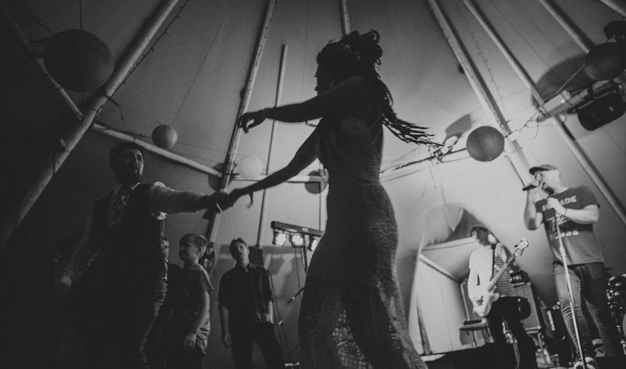 The bride dancing with the groom on the dancefloor in the tipi