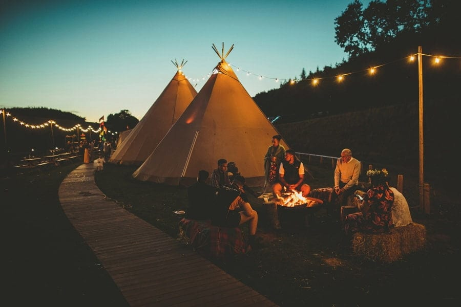 Wedding guests sit around an open fire outside the tipi at Hadsham Farm