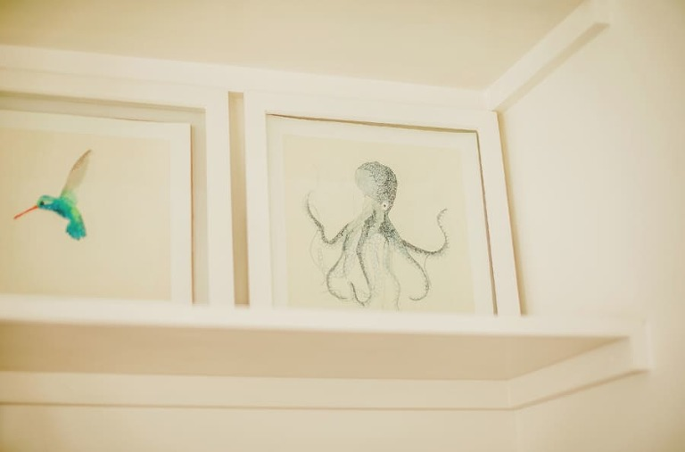 The bride and grooms framed prints on a shelf in the house