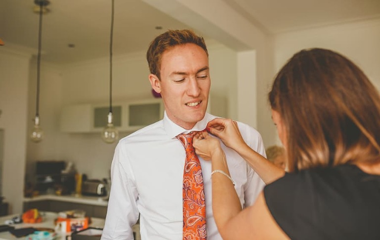 The grooms sister helps the groom with his collar and tie