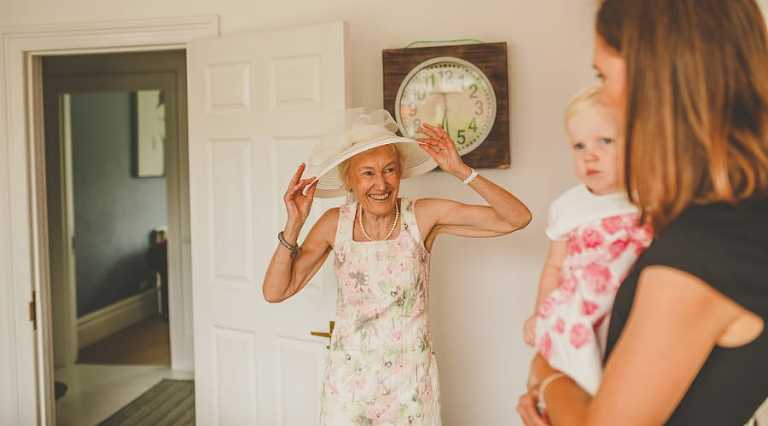 The grooms mother straightens her hat and smiles at her daughter and granddaughter in the kitchen