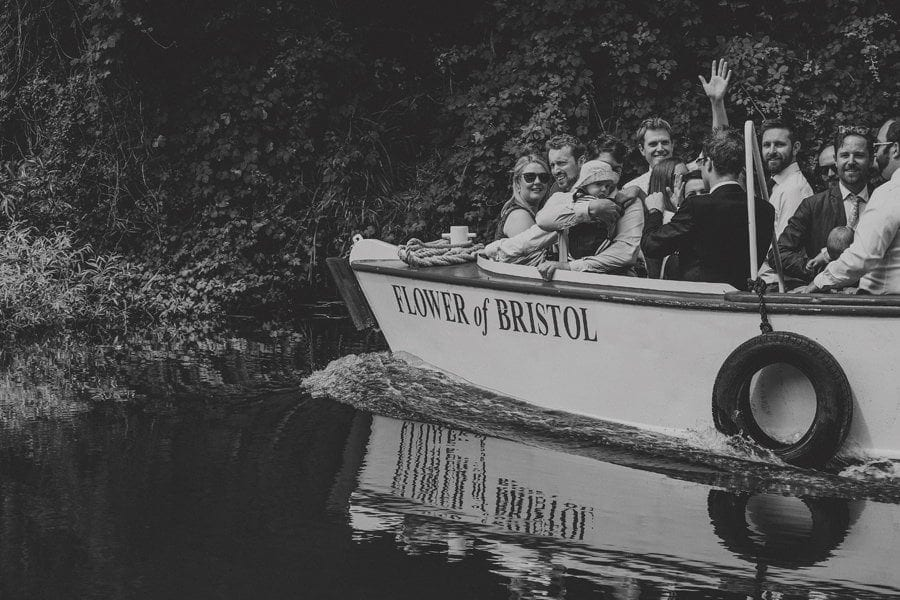 Wedding guests wave on another wedding boat on the canal in Bristol