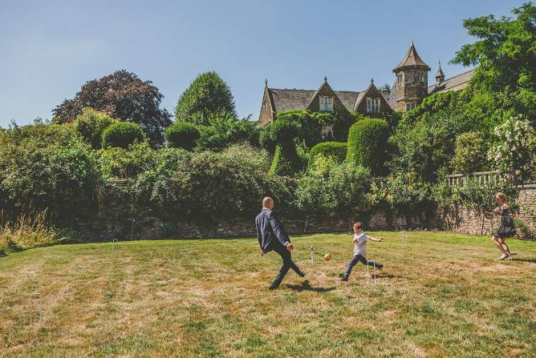 A wedding guest plays football with his son and his wife outside the estate of Hanham Court