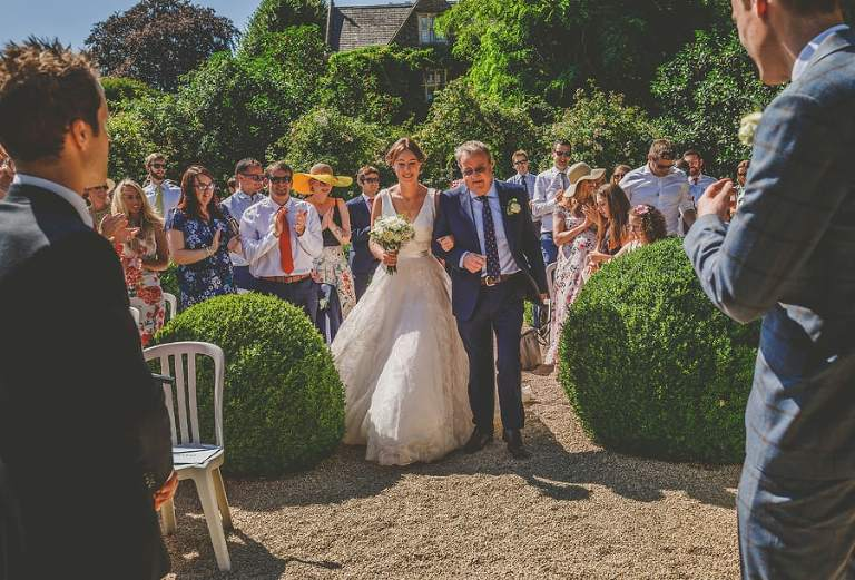 The bride and her father walk towards the groom for the outdoor ceremony at Hanham Court