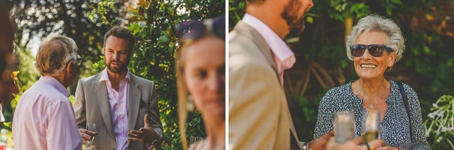 Wedding guests chat to each other in the gardens at Hanham Court