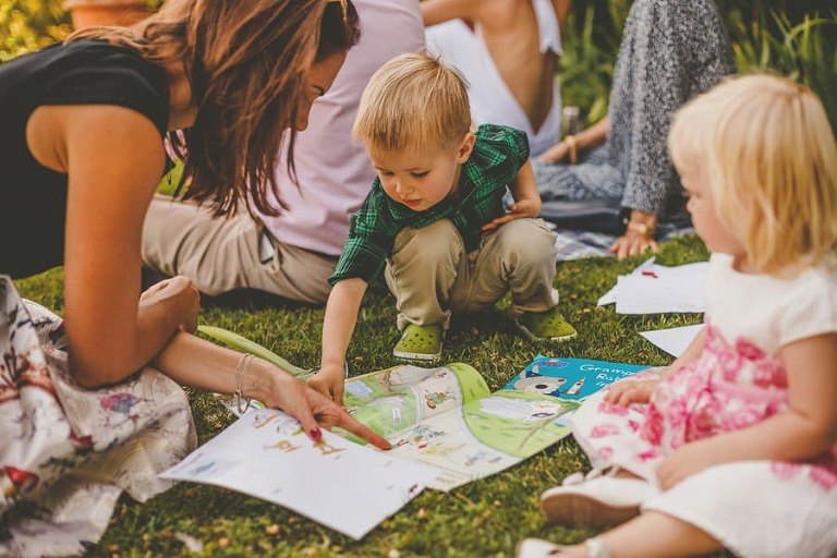 A little boy reads a book with his mother on the grass at Hanham Court