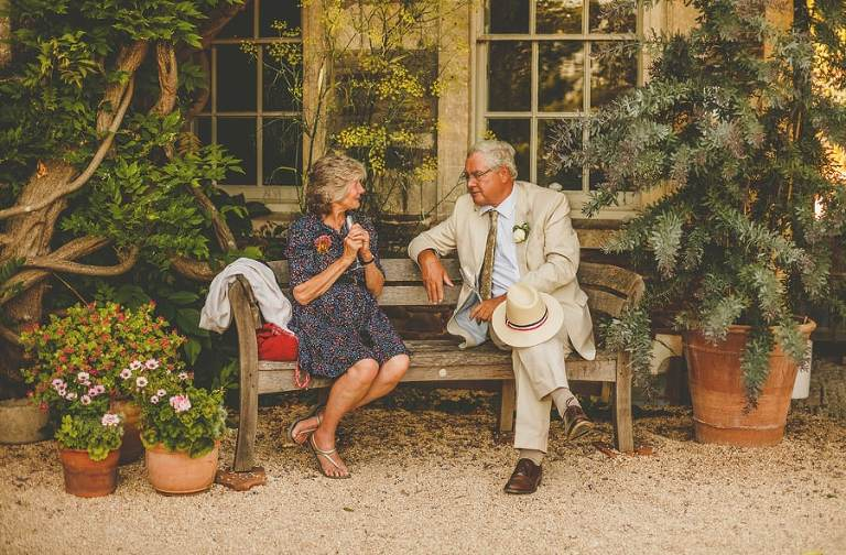 The bride and groom's family sit down on a bench outside the house and talk to each other