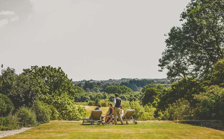 Wedding guests sit on sun loungers in the gardens and talk to each other