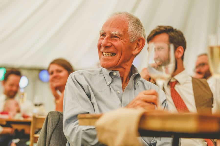 A wedding guest sits at the table in the marquee and smiles as he listens to the groom's speech