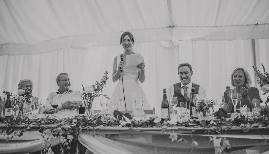 The bride stands up and delivers her speech to the wedding party in the marquee