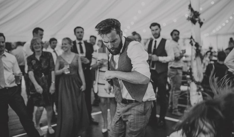 A wedding guest on the dancefloor in the marquee at Hanham Court