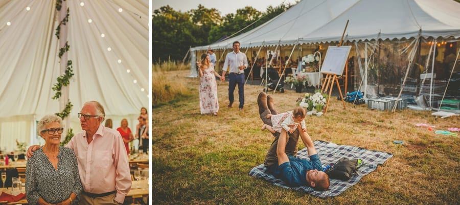 A wedding guest lies on a picnic rug and lifts his daughter in the air next to the marquee at Hanham Court