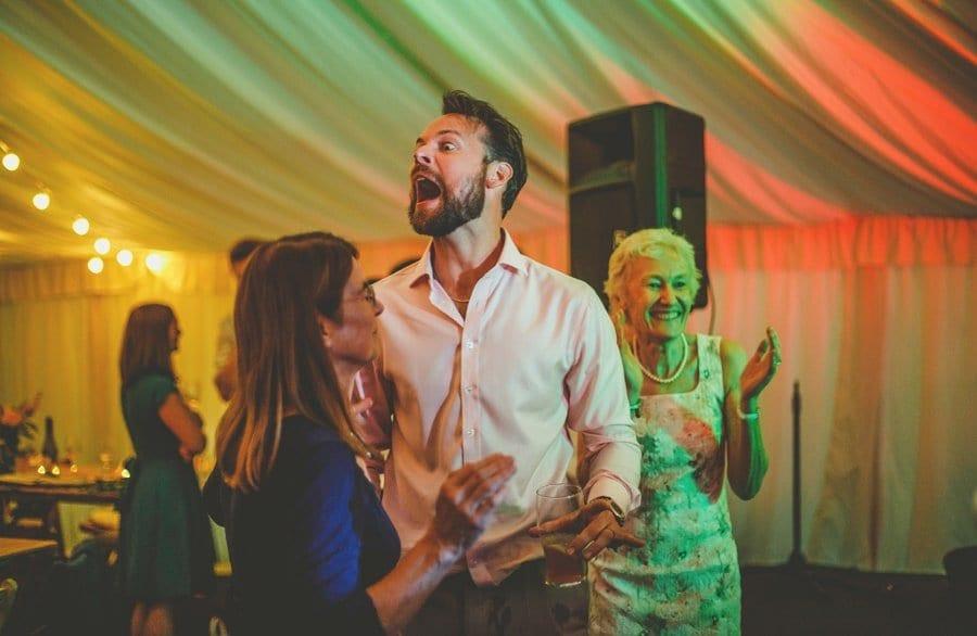 A wedding guest dancing with his wife shouts across the dancefloor