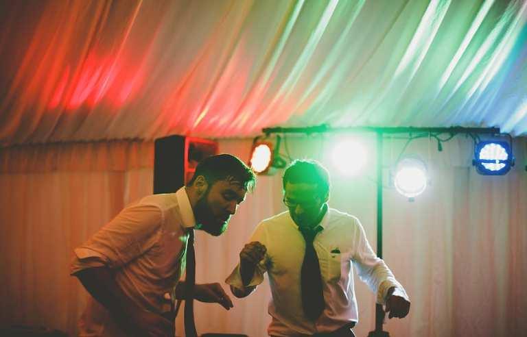 Two men dancing on the dancefloor in the marquee at Hanham Court in Bristol