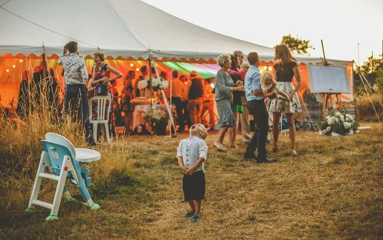 A little boy looks up to the sky outside the marquee at Hanham Court