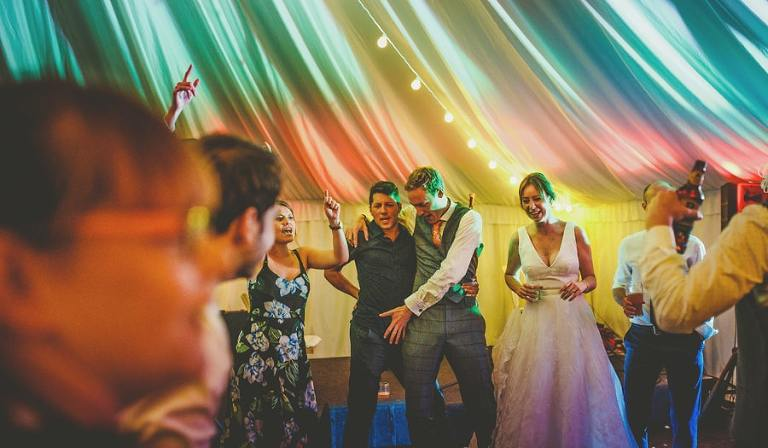 The bride and groom dancing with a wedding guest in the marquee