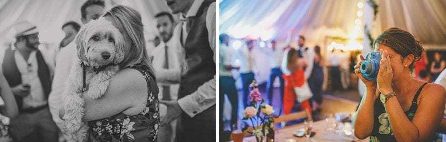 A wedding guest holds the bride and grooms dog in her arms and a wedding guest takes a photograph
