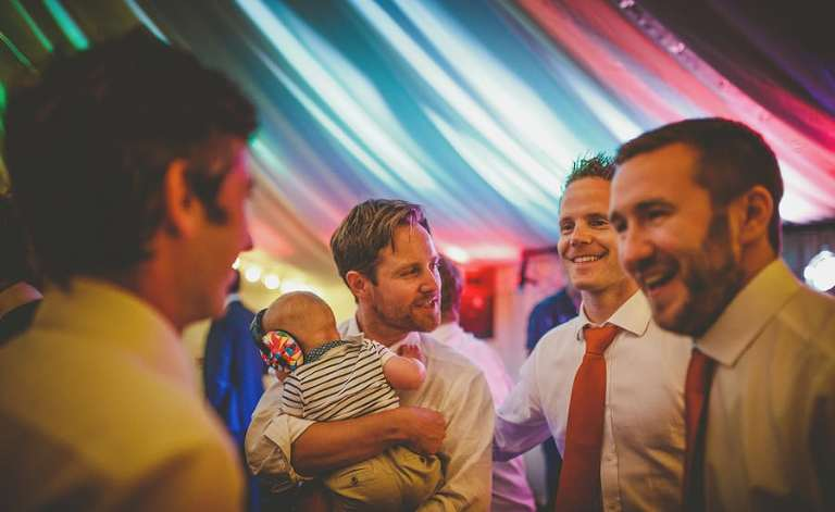 A wedding guest holds his baby in his arms and chats with friends in the marquee