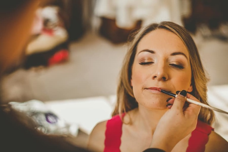 The bride has lipstick applied onto her lips by the makeup artist