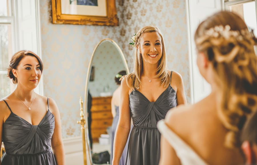 The bridesmaids smile at the bride at Kings Weston House