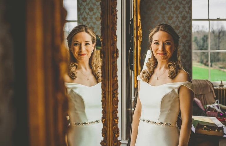 The bride poses for a photograph next to a window in the master bedroom at Kings Weston House in Bristol