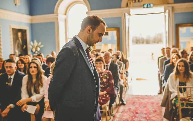 The groom looks at the floor as he nervously awaits the bridal party