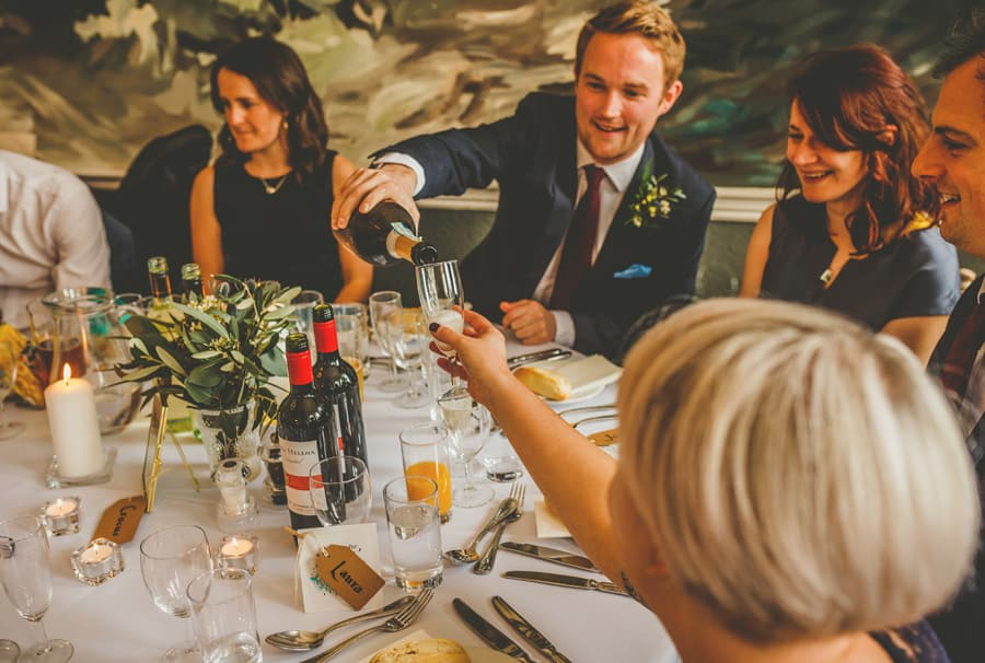A wedding guest pours wine into a ladies glass as they sit around the wedding table