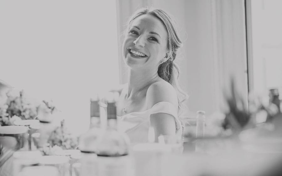 The bride laughs at her father's wedding speech as she sits at a table
