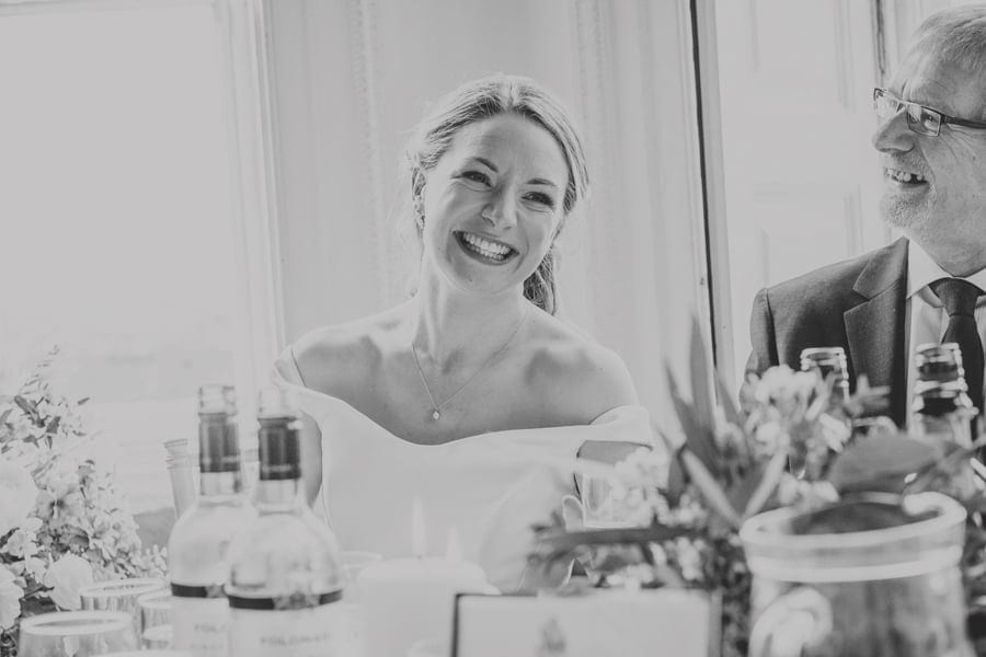 The bride smiles as she listens to the best mans speech at Kings Weston House
