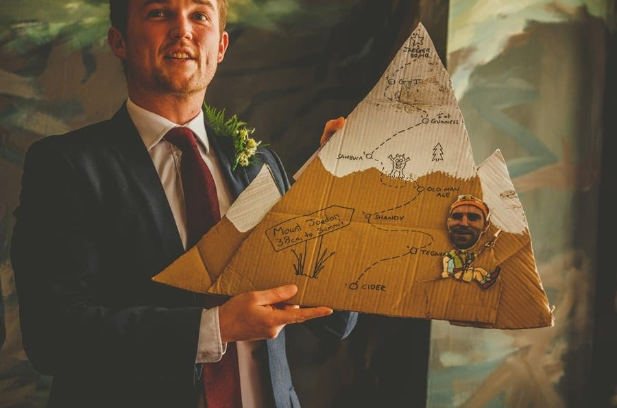 The best man holds up a cardboard cut out for the bride and groom