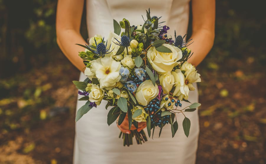 The bride holds her flower bouquet in both hands
