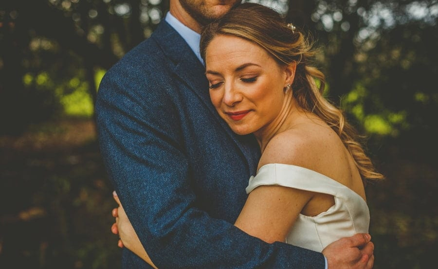 The bride places her arms around the groom and places her head on his chest