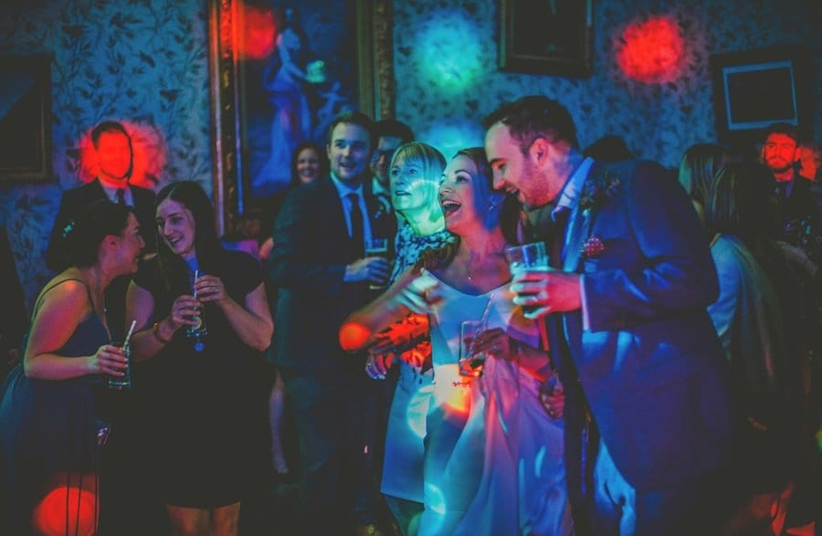 The bride and groom stand next to each other on the dancefloor at Kings Weston House
