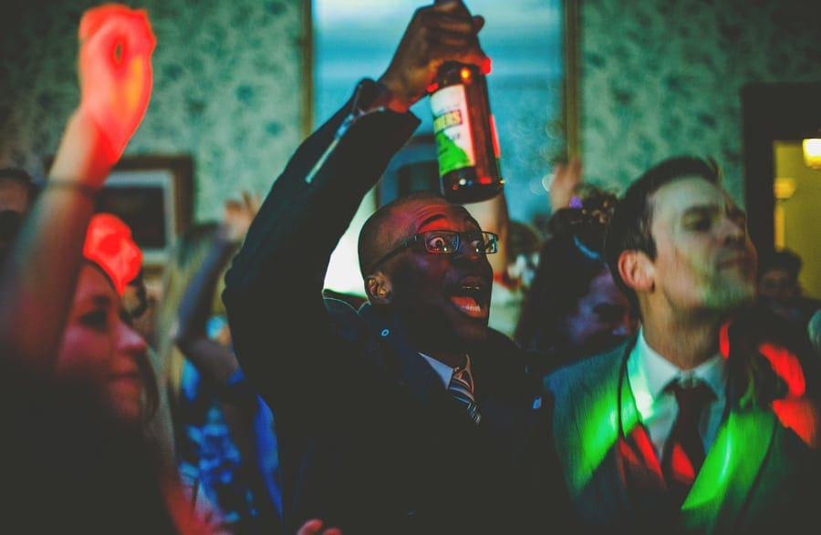 A wedding guest holds up a bottle of beer in his right hand on the dancefloor