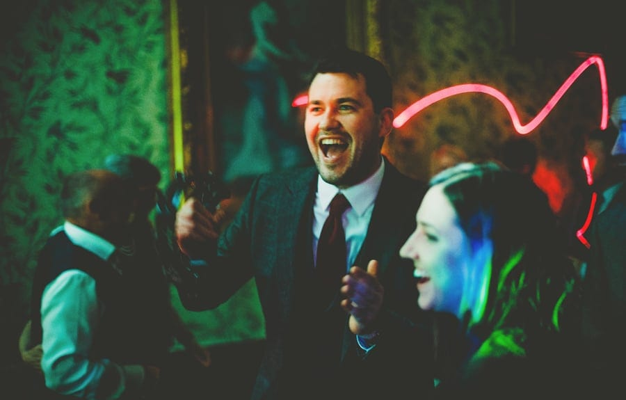 A wedding guest laughs with a friend on the dancefloor