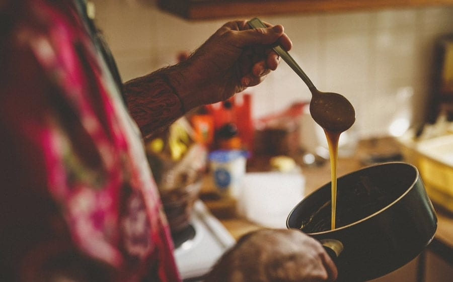 A wedding guest drips treacle from a spoon into a large pan in the kitchen of one of the cottages