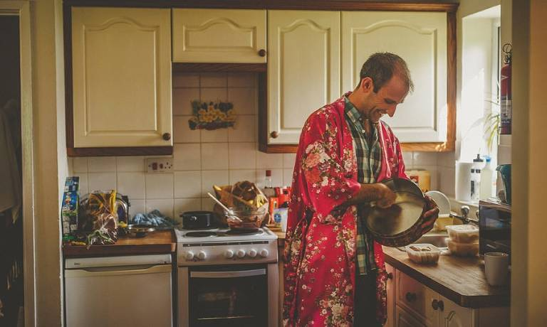 A man wearing a red silk nightgown cleans a baking tray in the kitchen