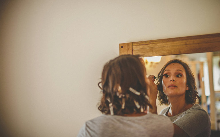 A bridesmaid puts eyeliner on her eyelashes as she looks into a large mirror hanging from a wall