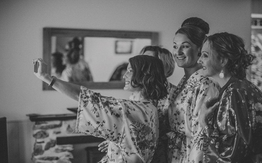 A bridesmaid holds up a mobile phone and takes a photograph of herself and her friends in the cottage