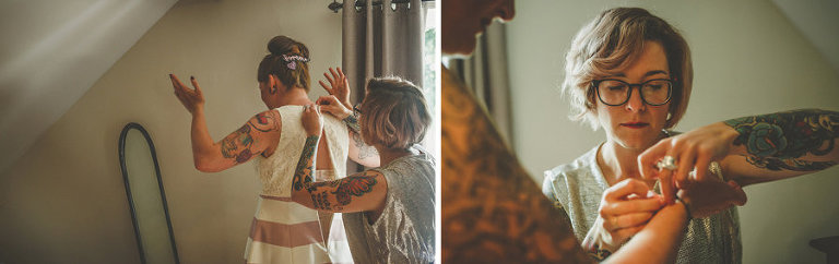 A bridesmaid helps the bride put on her dress in the bedroom of a cottage
