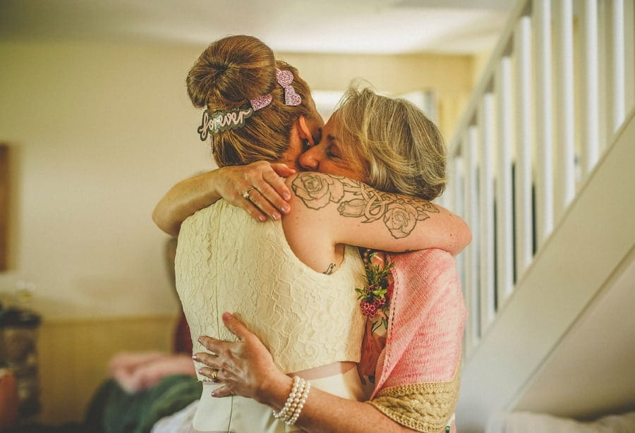 The bride and her mother hug each other in the cottage at Little Quarme in Minehead, Somerset