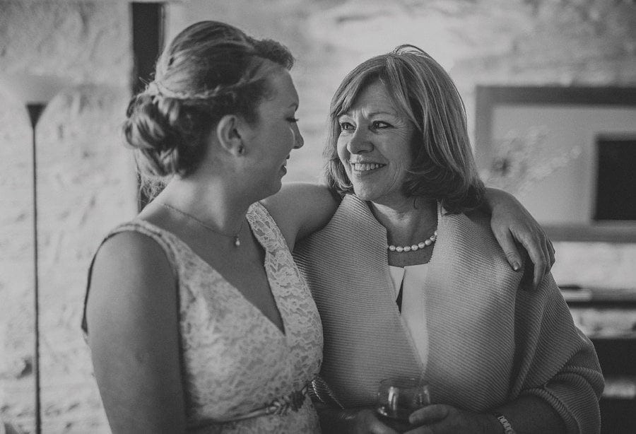 The bride puts her arm around her mother and laughs with her